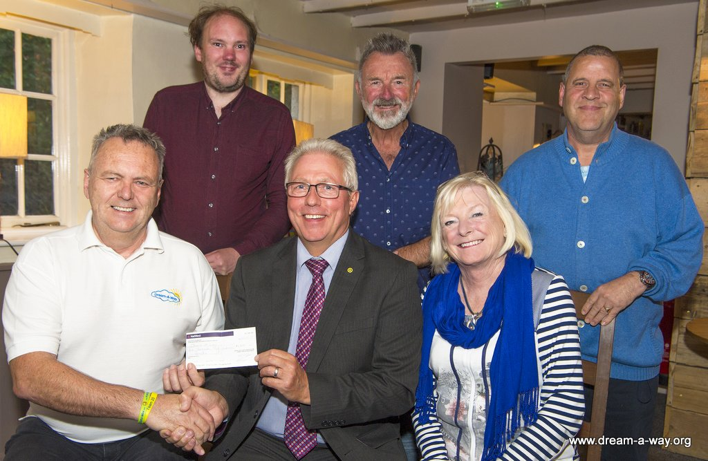 Photo of Paul Willis a senior manager at Gregory Distribution and former chairman of the RHA (Road Haulage Association) North Devon Sub Region Group presenting a cheque for £1,200 to Jeff Merrett MBE and other Dream-A-Way team members