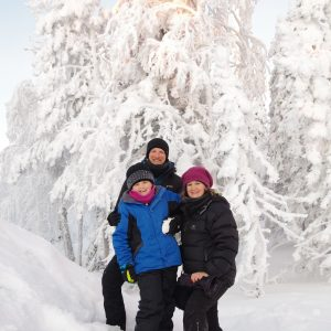 Zack, mum & dad in front of bright, white snow covered trees.