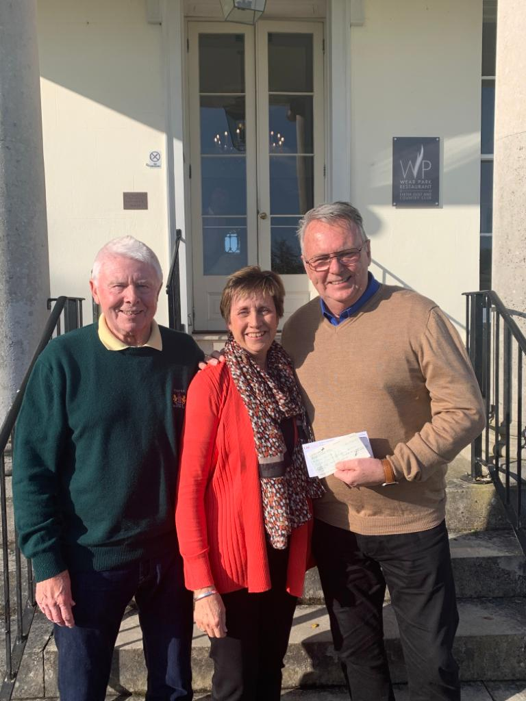 Colin and Jackie Follett with Jeff standing in front of the main entrance of the club in the sunshine, smiling.