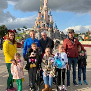 Group shot of the Holman family at Disneyland Paris with the towers of The Magic Kingdom in the background