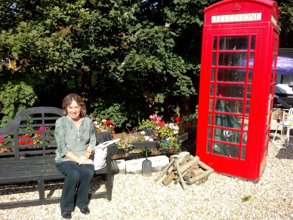 Elaine sat on a bench by an old red phone box